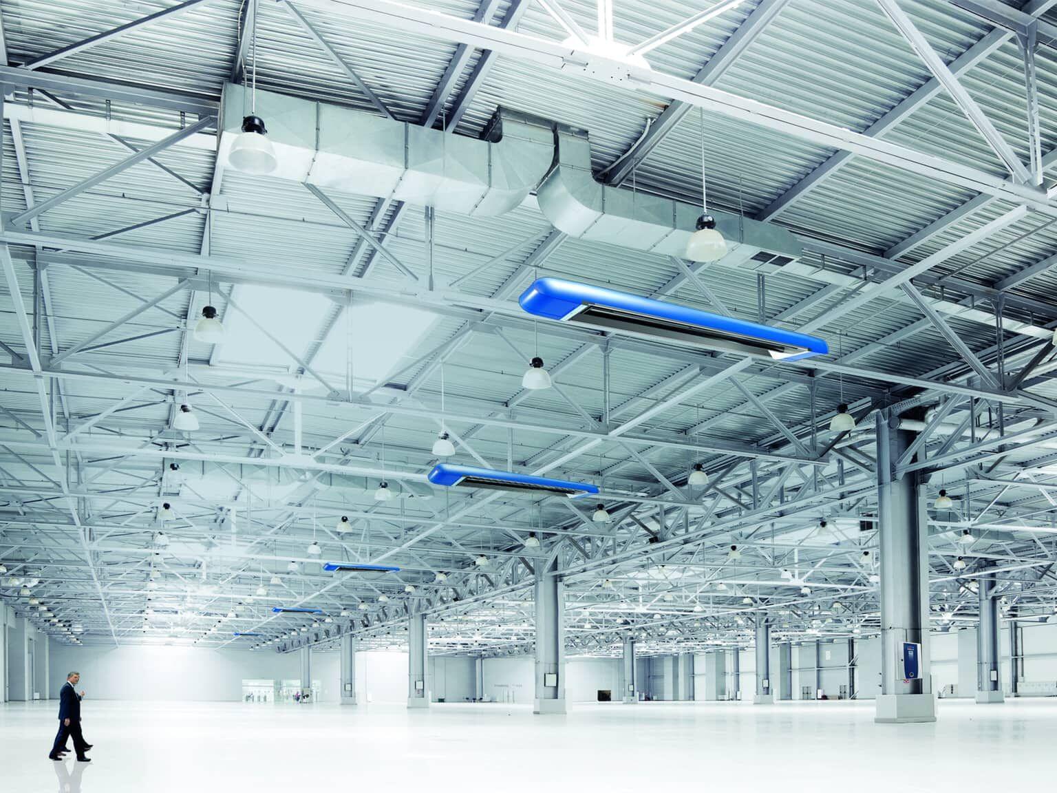 Ein Mann geht alleine durch eine große Industriehalle mit Dunkelstrahlern