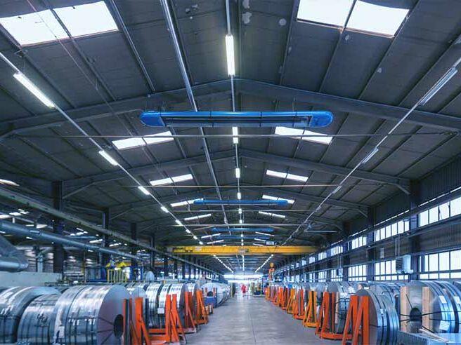 Weitwinkelaufnahme einer Industriehalle von innen, die mit einer Infrarot-Hallenheizung beheizt wird.