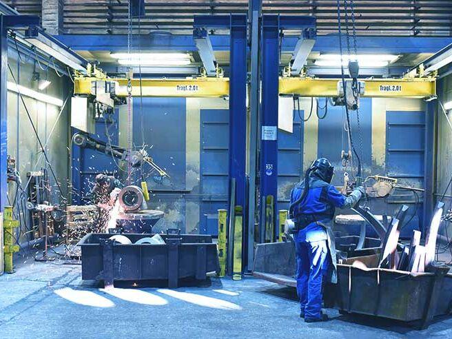 Arbeiter in einer Industriehalle - schweißen und flexen von Werkstücken/ Gussteilen aus Metall