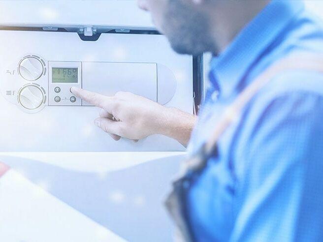 Mann überprüft Heizungstemperatur in der Produktionshalle.