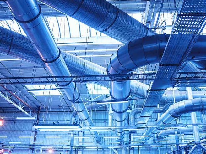 Leitungen an der Decke einer Halle, die die Abwärme aus Prozessen weiterleiten.