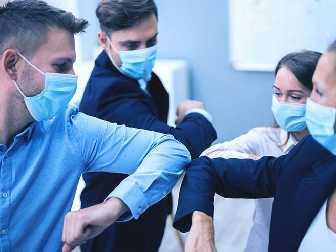 Angestellte mit Mundschutz machen einen Ellbogenstoß, um Krankheitsübertragung zu vermeiden