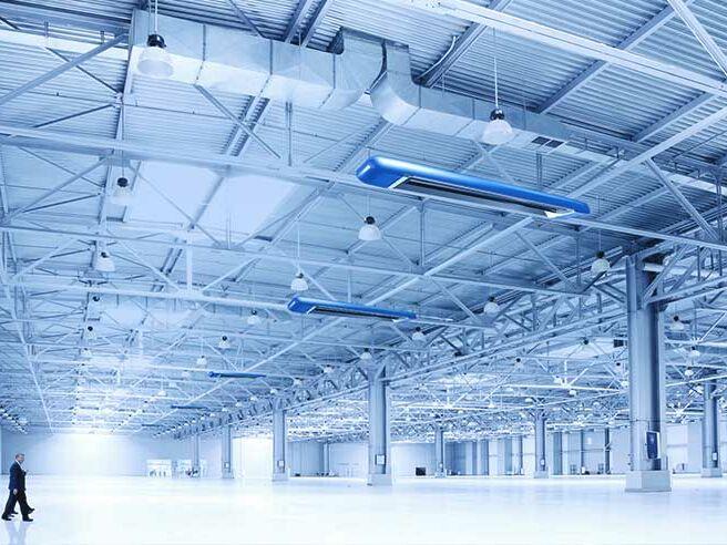 Riesige leere Produktionshalle, die mit Dunkelheizstrahlern beheizt wird.