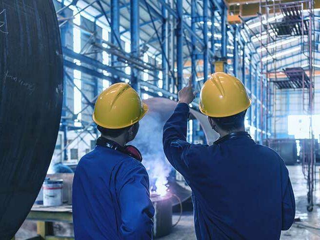Zwei Experten beraten sich über die Heizungswartung in einer Halle für Fertigung von Industriekesseln.
