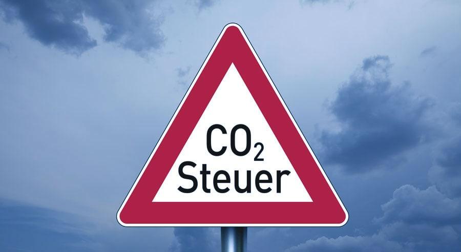 Straßenschild in Form eines Vorfahrt gewären Schildes, mit der Aufschrift CO2-Steuer.