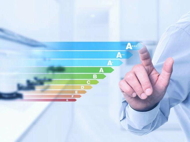Eine Hand die auf eine Darstellung der Energieeffizienzklassen von einem Heizsystem zeigt.