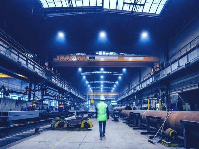 Bauleiter steht in einer Produktionshalle und plant neue Heizung für die Hallen.