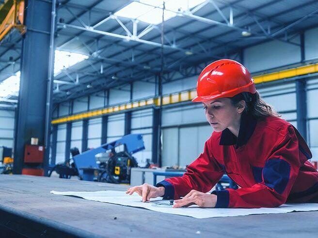 Arbeiterin, die einen Konstruktionsplan erstellt für einen Kunden, der Dunkelstahler kaufen möchte.